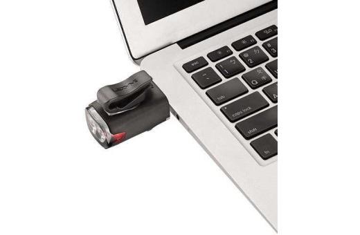 Bilden visar Lezyne KTV Drive framlampan när den laddas via USB porten på en laptop.